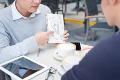 Outdoor portrait of two young entrepreneurs working at coffee sh. Op Royalty Free Stock Photos