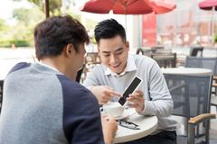 Outdoor portrait of two young entrepreneurs working at coffee sh. Op Stock Image
