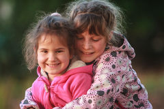 Outdoor portrait of two young happy children, girls - sisters - Stock Image