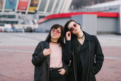 Outdoor portrait of two young and stylishly dressed girls with glasses on the background of the urban landscape. Stock Photo