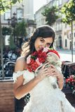 Outdoor portrait. Vertical portrait of the beautiful bride with lovely smile holding the wedding bouquet of red and pink Stock Photography