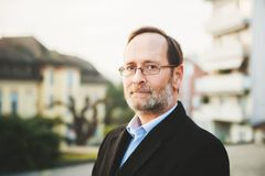 Outdoor portrait of 50 year old man. Wearing black coat and eyeglasses Stock Image
