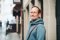 Outdoor portrait of 50 year old man. Wearing blue hoody and eyeglasses Stock Photos