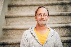 Outdoor portrait of 50 year old man. Wearing grey hoody and eyeglasses royalty free stock photos