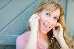 Outdoor Portrait of Young Adult Brown Eyed Woman Listening To Mu. Sic with Earphones Stock Photos