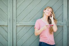Outdoor Portrait of Young Adult Brown Eyed Woman Listening To Mu. Sic with Earphones on Her Smart Phone Royalty Free Stock Image