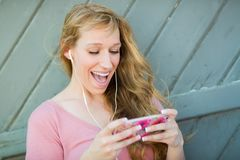 Pretty Young Adult Brown Eyed Woman Listening To Mu. Outdoor Portrait of Young Adult Brown Eyed Woman Listening To Music with Earphones on Her Smart Phone Royalty Free Stock Photos