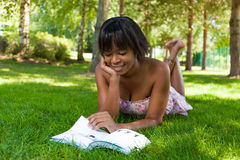 Outdoor portrait of young black woman reading a book. Outdoor portrait of young african american woman lying down on the grass reading a book Royalty Free Stock Photo