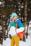 Outdoor portrait of young attractive woman with bagpack posing in the park. Model wearing stylish warm clothes. City royalty free stock image