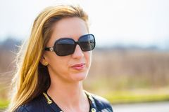 Fashion girl in sunglasses on minimalist seasonal background, soft smile. Outdoor portrait of young attractive woman with sunglasses on a seasonal weather royalty free stock images