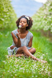 Outdoor portrait of a young beautiful african amer. Ican woman blowing a dandelion flower - Black people stock photography