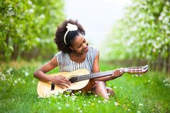 Outdoor portrait of a young beautiful african american woman playing guitar - Black people royalty free stock photos