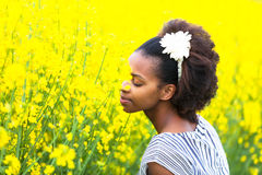 Outdoor portrait of a young beautiful african american woman in. A colza field - Black people royalty free stock photography