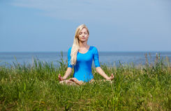 Blonde girl gymnast outdoors. Outdoor portrait of young beautiful blonde woman gymnast sitting in yoga lotus pose on green grass Royalty Free Stock Photography