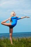 Blonde girl gymnast outdoors Stock Image