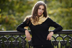 Outdoor portrait of young beautiful brunette woman with wavy long hair stares into camera posing against cast-iron fence with blur. Outdoor portrait of young Stock Image