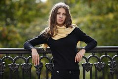 Outdoor portrait of young beautiful brunette woman with wavy long hair stares into camera posing against cast-iron fence with blur. Outdoor portrait of young Stock Photography