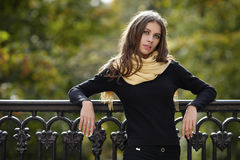 Outdoor portrait of young beautiful brunette woman with wavy long hair stares into camera posing aginst cast-iron fence with blurr. Outdoor portrait of young Stock Photo