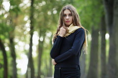 Outdoor portrait of young beautiful brunette woman with wavy long hair stares into camera posing on the park with blurry forest ba Stock Image