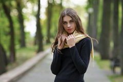 Outdoor portrait of young beautiful brunette woman with wavy long hair stares into camera posing on the park path. Outdoor portrait of young beautiful brunette Stock Image