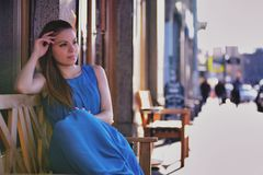 Outdoor portrait of young beautiful caucasian sits on bench on street in St.Petersburg, Russia Royalty Free Stock Images