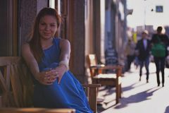 Outdoor portrait of young beautiful caucasian sits on bench on street in St.Petersburg, Russia Stock Image
