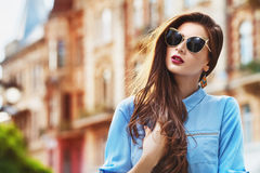 Outdoor portrait of a young beautiful confident woman posing on the street. Model wearing stylish sunglasses. Girl stock image