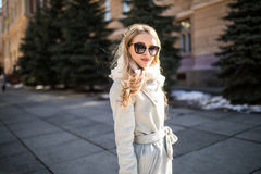 Outdoor portrait of a young beautiful fashionable happy lady posing on a street of the old city. Model wearing stylish clothes. Gi Stock Photo