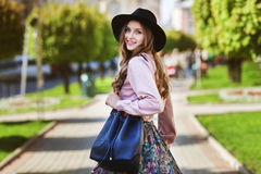 Outdoor portrait of young beautiful fashionable happy smiling lady walking on the street. Model wearing stylish fedora. Outdoor portrait of young beautiful Royalty Free Stock Photography