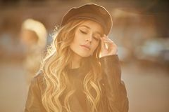 Outdoor portrait of young beautiful fashionable and sensual woman in black leather jacket and stylish hat with makeup and closed e stock image