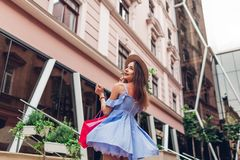 Outdoor portrait of a young beautiful fashionable woman dancing with shopping bag on city street stock photography