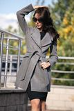Outdoor portrait of a young beautiful fashionable woman, outdoors. A model dressed in a stylish gray coat, sunglasses. The concept royalty free stock photo