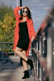 Outdoor portrait of a young beautiful fashionable woman, outdoors. The model, dressed in a stylish orange coat Royalty Free Stock Image