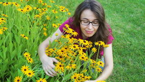 Outdoor portrait of young beautiful fashionable woman posing near flowers. Model with stylish glasses stock video footage