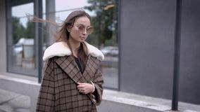 Outdoor portrait of young beautiful fashionable woman posing in street. Model wearing stylish brown coat. Female fashion stock footage