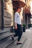Outdoor portrait of a young beautiful fashionable woman walking out of store on city street stock photo