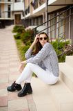 Outdoor portrait of young beautiful girl posing in street. Model wearing stylish sunglasses, stripped black-white blouse royalty free stock photo