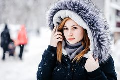 Outdoor portrait of young beautiful girl wearing in black jacket with a hood . Model posing in street. Winter holidays concept royalty free stock images