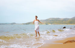 Girl running in waves Stock Photography