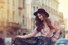 Outdoor portrait of young beautiful happy lady posing on street. Model wearing stylish clothes. Girl looking down. Sunny Royalty Free Stock Photo