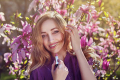 Outdoor portrait of a young beautiful happy smiling lady using lipstick near magnolia tree with flowers. Model looking Royalty Free Stock Image
