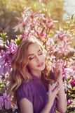 Outdoor portrait of a young beautiful lady using perfume near magnolia tree with flowers. Model closed her eyes. Girl Stock Photo