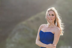 Outdoor portrait of young beautiful woman in blue gown posing on Royalty Free Stock Photos