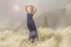 Outdoor portrait of young beautiful woman in blue gown posing on Royalty Free Stock Images