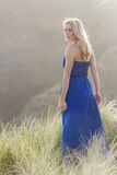 Outdoor portrait of young beautiful woman in blue gown posing on Stock Photo