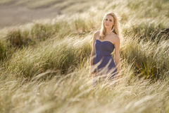Outdoor portrait of young beautiful woman in blue gown posing on Royalty Free Stock Photography
