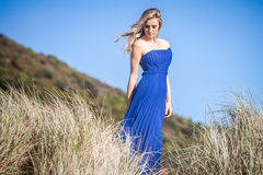 Outdoor portrait of young beautiful woman in blue gown posing on Stock Photography