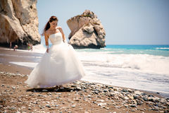 Outdoor portrait of young beautiful woman bride in wedding dress on beach. Petra tou Romiou - Aphrodite's Rock. Stock Image