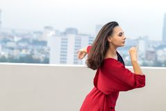 Outdoor portrait of young beautiful woman dancing on the rooftop royalty free stock photography