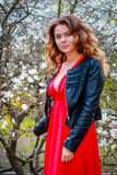 Outdoor portrait of a young beautiful woman near magnolia tree with flowers Stock Photo